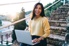 Smiling Asian Woman Working On Laptop On Stairs