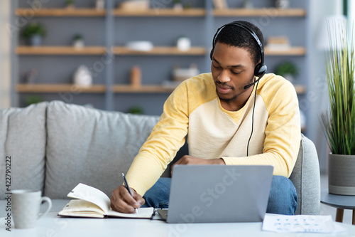 Fototapeta Black guy attending online training from home, taking notes obraz