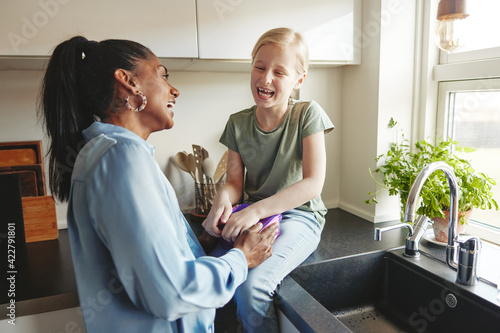 Fototapeta Mom and her little daughter laughing in their kitchen obraz