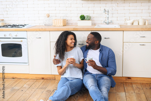 Young multiracial couple drinking coffee sitting on the kitchen floor, celebrate Fototapeta