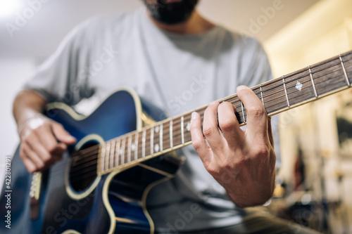 Fototapeta Young man practicing acoustic guitar at home.Focus selective