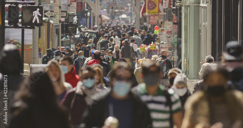 Fototapeta Anonymous crowd of people walking street wearing masks during Covid 19 pandemic in New York City obraz