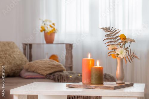 Fototapeta burning candles with autumn decor on white table at home obraz