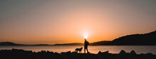 Silhouette Of Hiker Man Walking On The Rocks In A Coastline On The Beach With His Dog. Background With Beautiful Sunset.