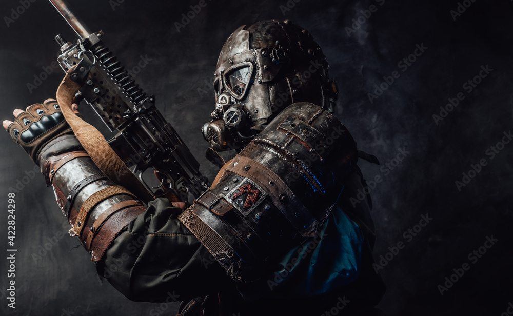 Fototapeta Grimy hunter with gas mask and custom gun in dark background