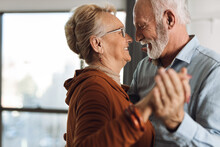 Happy Mature Couple Having Fun While Dancing At Home
