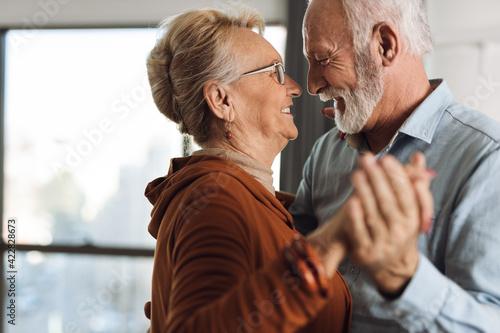 Fototapeta Happy mature couple having fun while dancing at home obraz