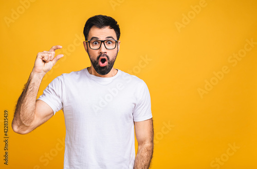 Happy bearded man in casual makes tiny gesture, shows something very little, smiles gladfully, has cheerful expression, isolated over yellow background. People and size.