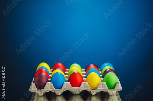 Obraz Easter festive multicolor eggs carton, blue background - fototapety do salonu
