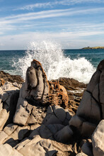 A Wave Crashes Into The Rocky Shoreline Of Makaluapuna Point Near A Vertical Rock That Is Part Of The Dragon's Teeth