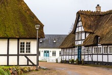 Traditional Old Country Houses With Thatched Straw Roof On Street In Denmark