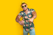 Young sportve man on vacation wearing floral summer shirt over yellow background success sign doing positive gesture with hand, thumbs up smiling and happy. Cheerful expression and winner