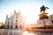 Wide Angle View Of Milan Cathedral (Duomo Di Milano) With Sun Illuminating The Empty Square, Cordoned Off Statue, Postcard