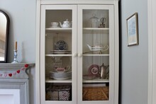 White Wooden Cupboard With Clear Glass Used To Store Teapots, Plates, Tea Cups And Other Kitchen Accessories.