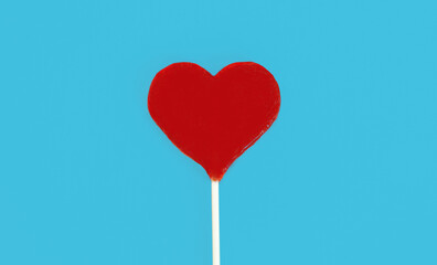 Close up sweet red heart shaped lollipop on a blue background