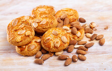 Closeup Of Crispy Macaroons With Dried Almonds On Wooden Table