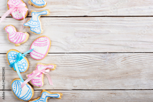 Fototapeta Easter frosted cookies in shape of egg chicken and rabbit on white wooden table background flat lay horizontal mockup with copy-space obraz