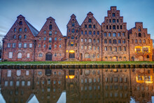 The Old Salzspeicher Reflecting In The Trave River At Dawn, Seen In Luebeck, Germany