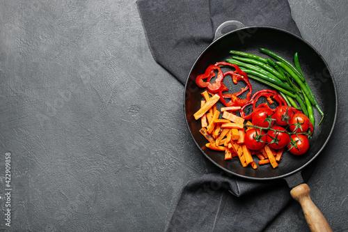Fényképezés Frying pan with tasty vegetables on dark background