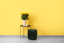Vase With Beautiful Yellow Roses On Table And Pouf Near Color Wall In Room