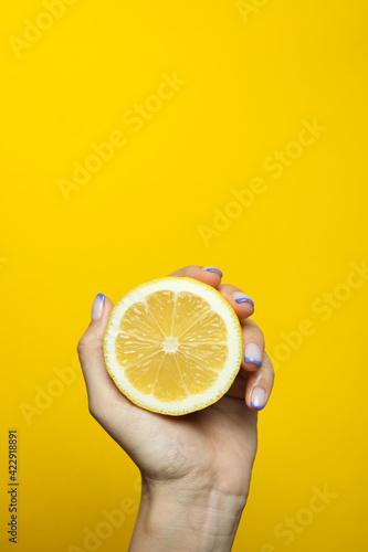 Fototapeta Female hand hold lemon on yellow background obraz