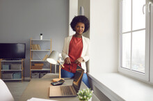 Young Successful African American Businesswoman In Office Portrait. Smiling Black Woman Entrepreneur Standing Next To Window Rest After Hard Work Looking At Camera. Self-confidence And Success