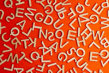 Wooden Cut Alphabet Letters On Orange Background