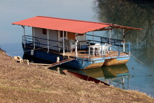 River Barge Converted Into River Boat House With Improvised Homemade Roof And Terrace With White Plastic Chairs And Tables Left At Local River Bank Covered With Dry Grass On Cold Sunny Winter Day