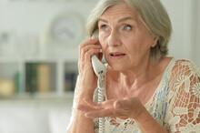 Portrait Of Upset Senior Woman Calling Doctor