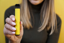 Yellow Disposable Electronic Cigarette In Female Hand. Bright Yellow Background