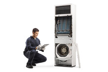 Repairman Kneeling In Front Of A Self Standing Air Conditioner With Removed Cover For Service