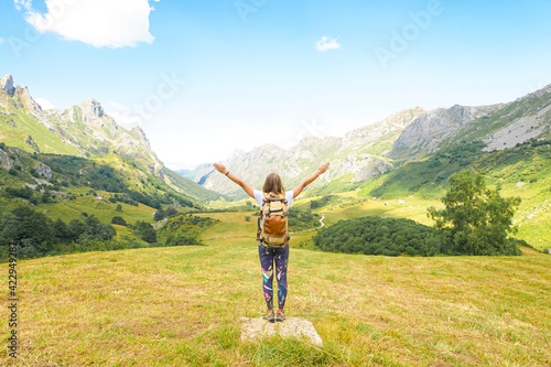 A girl with a backpack and arms wide open in the air is looking to the mountains with a blue sky and white clouds фототапет