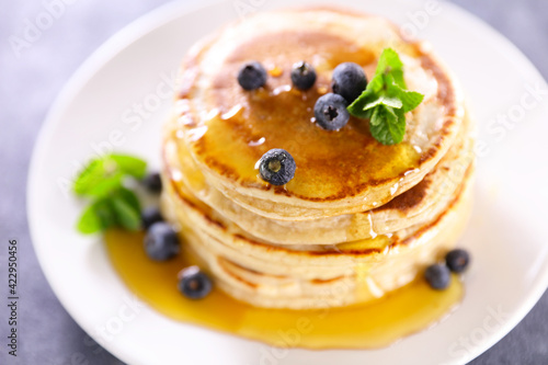 stack of pancakes with blueberries and syrup