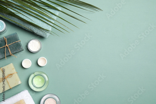 Different personal care products on teal background, flat lay. space for text