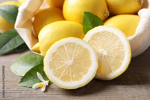 Photo Many fresh ripe lemons with green leaves and flower on wooden table, closeup