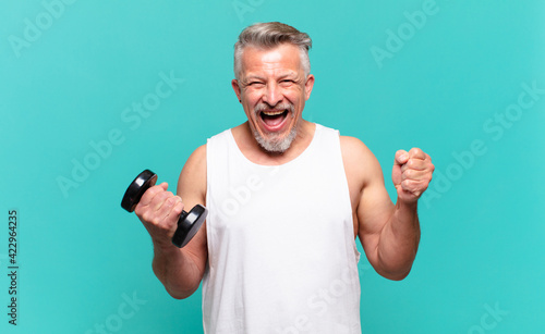 Fototapeta senior athlete man feeling shocked, excited and happy, laughing and celebrating success, saying wow! obraz