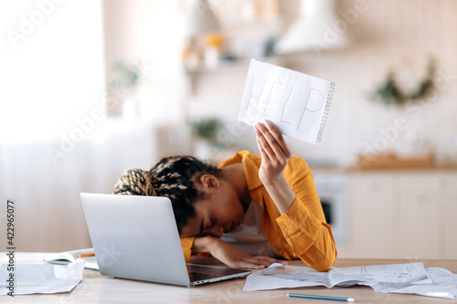 Fototapeta A frustrated African American female student is tired of studying at home, lies at her desk and holds a leaflet with the inscription help. Freelancer young woman need a rest from remotely work obraz
