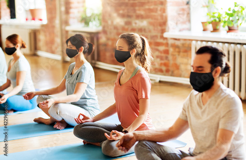 Fotografie, Tablou group of people in masks doing yoga at studio