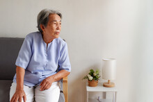 Elderly Asian Woman With Grey Hair Sitting Lonely On The Sofa, Aging Society Sad And Lonely Concept, With Copy Space For Text.