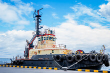 A Marine Tugboat Is Docked At The Pier. Tugboats Take International Ships Out Of Port To Continue Sailing