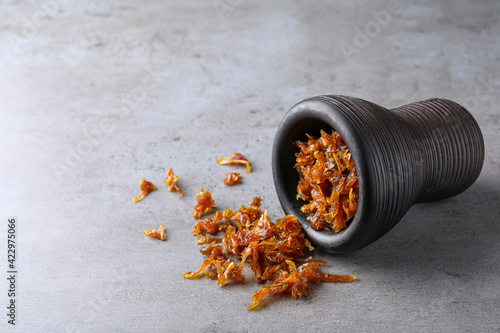 Modern hookah bowl with tobacco on grey table. Space for text