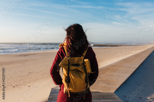 backpacker young caucasian woman relaxing at the beach at sunset Fototapeta