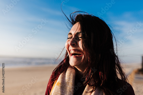 Fotografie, Tablou happy woman having fun at the beach on a windy day at sunset