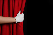 Woman Opening Red Front Curtains On Black Background, Closeup. Space For Text