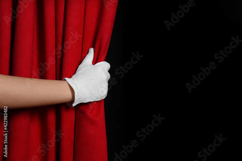 Fototapeta Woman opening red front curtains on black background, closeup
