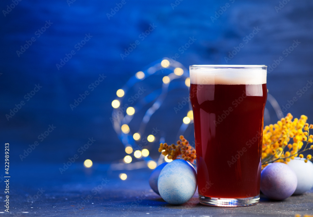 Limited edition craft beer pint glass on blue background, painted Easter eggs. The concept of celebrating Easter, copy space - obrazy, fototapety, plakaty