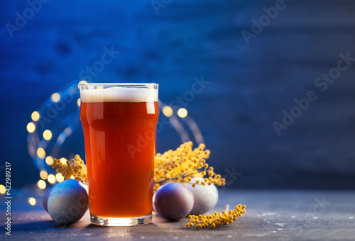 Fototapeta Limited edition craft beer pint glass on blue background, painted Easter eggs. The concept of celebrating Easter, copy space obraz na płótnie