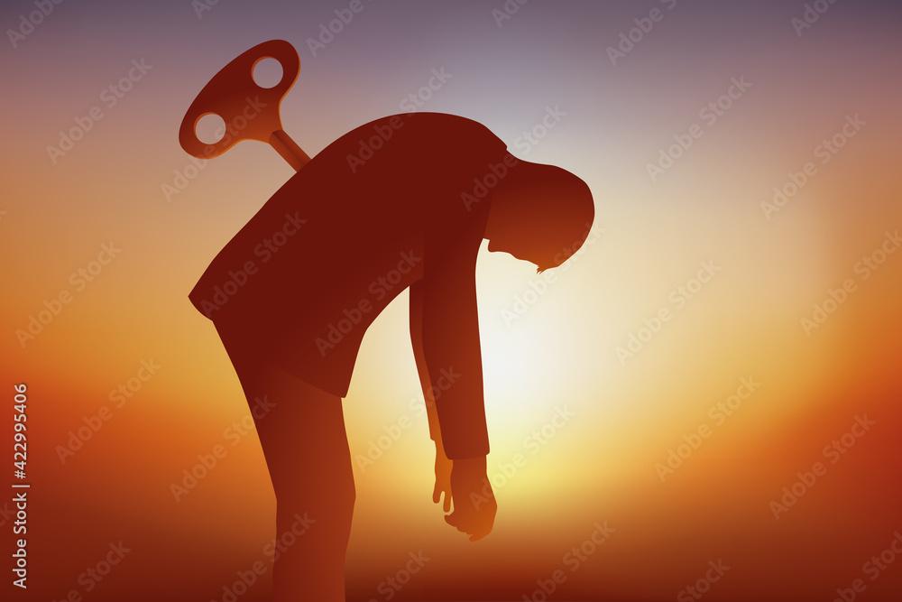 Fototapeta Concept du burnout avec un homme qui tombe d'épuisement faute d'avoir pu recharger ses batteries, symbolisé par une clé planté dans son dos.