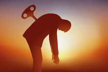 Concept Du Burnout Avec Un Homme Qui Tombe D'épuisement Faute D'avoir Pu Recharger Ses Batteries, Symbolisé Par Une Clé Planté Dans Son Dos.