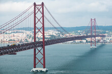 Modern Bridge On April 25 In Lisbon, The Capital Of Portugal, In Cloudy Cloudy Weather, Cars Drive On The Gigantic Bridge Across The Strait.